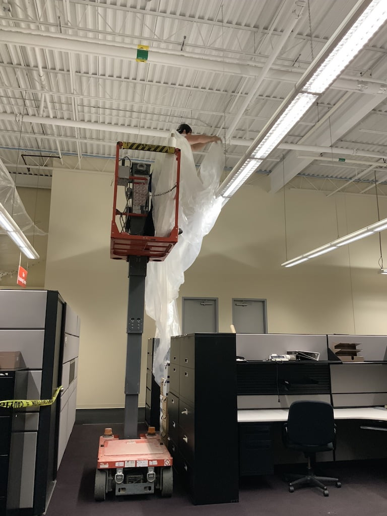 Ceiling containment crane worker
