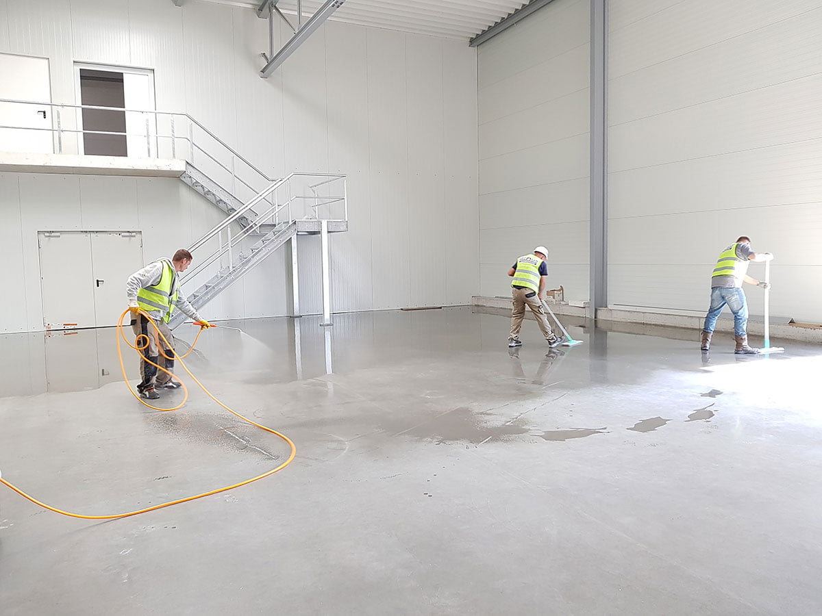 Cleaning, sealing and waxing a large concrete repair in garage foundation layer.
